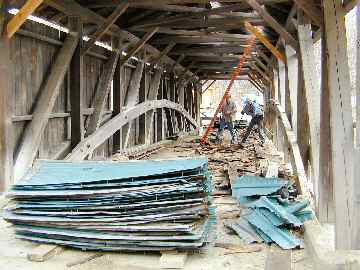 Removal of old metal roof reveals even older wooden shingles. Photo by Joe Nelson April 27, 2004.